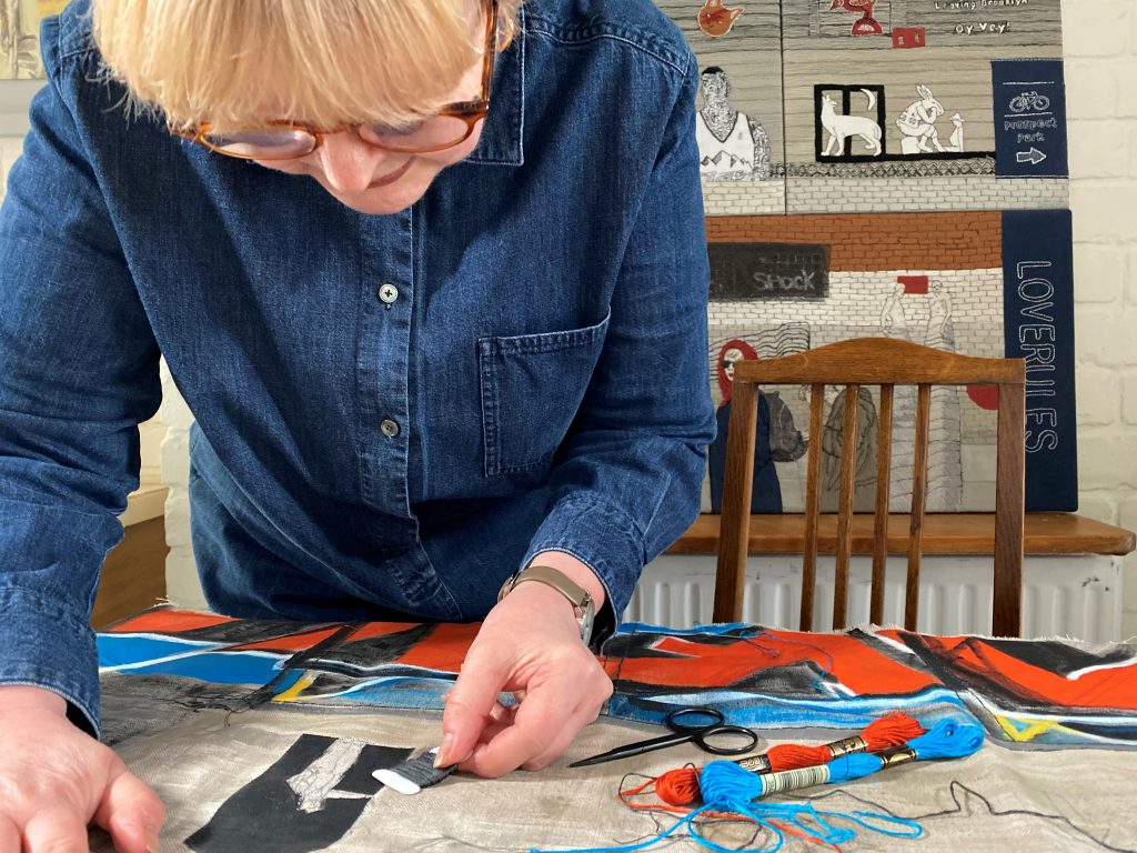 A lady creating some embroidered artwork.