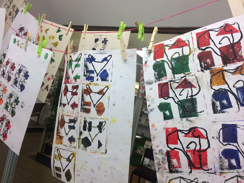 Some artwork using colourful shapes hung on a washing line