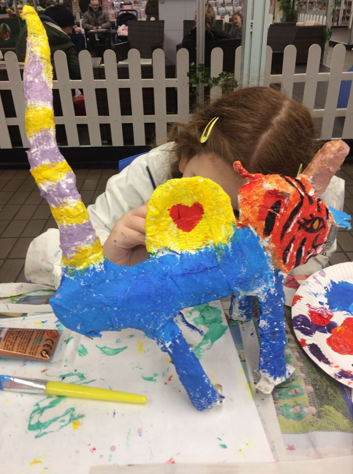 A girl making a model of a colourful tiger