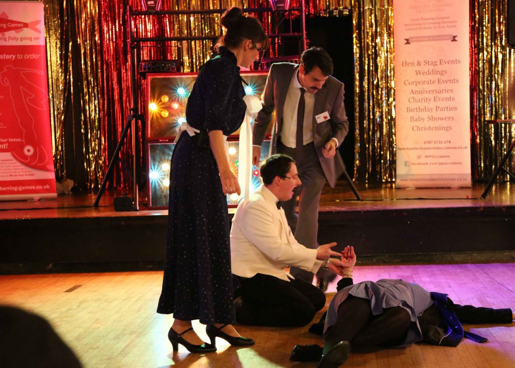 A murder mystery event. Three people are hovering over an apparent dead body.