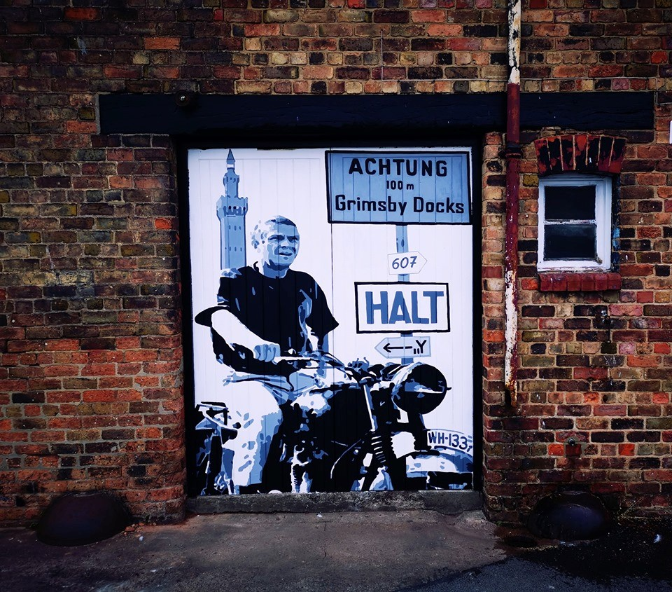 An art mural on a wall depicting a scene from 'The Great Escape' as a man on a motorbike is in front of the Dock Tower next to a sign that says 'Achtung 100m Grimsby Docks, Halt'.