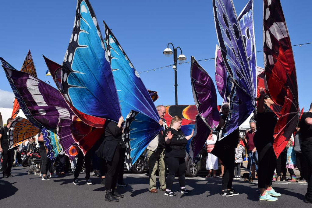 A festival with a crowd of people wearing large wings.