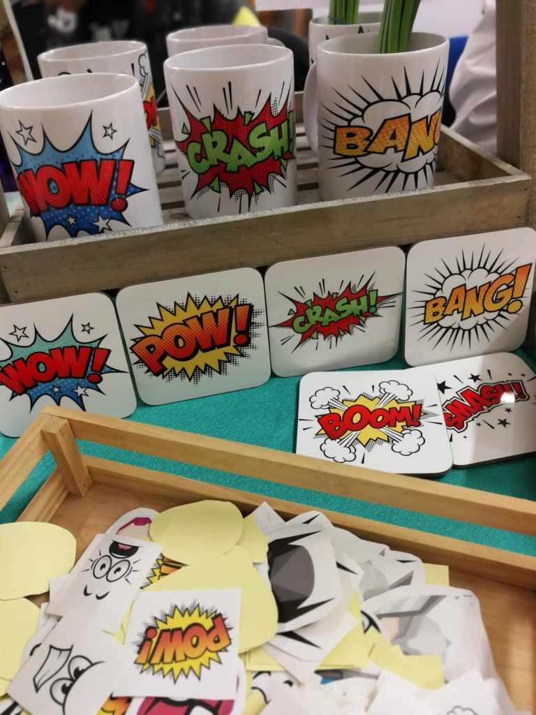 Mugs and place mats with the words wow!, pow!, crash! and bang! on.