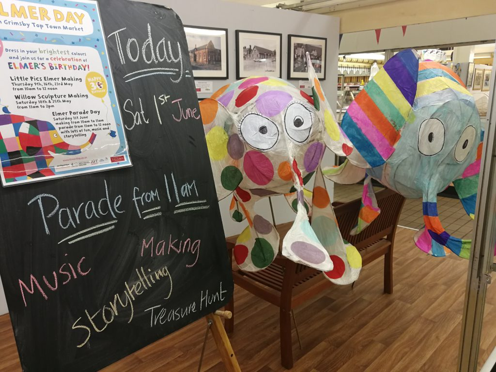 Colourful, artistic elephants within a gallery.