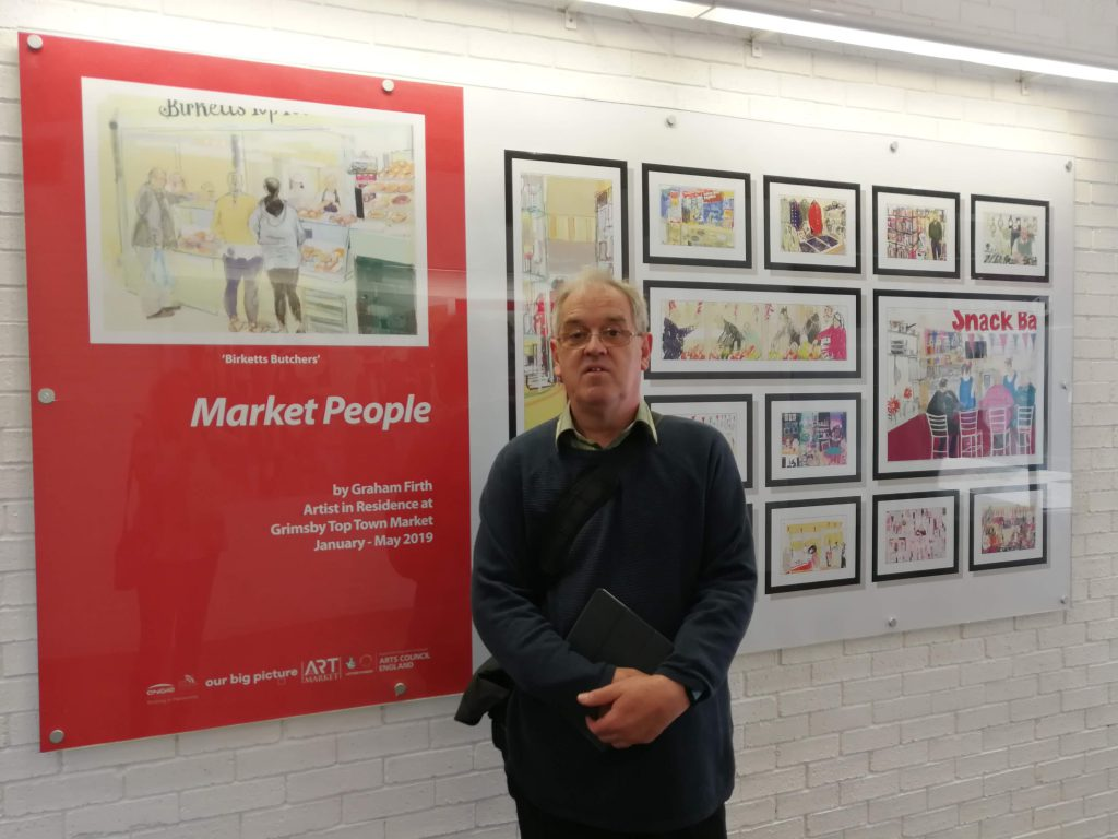A man with artistic drawings of a market.