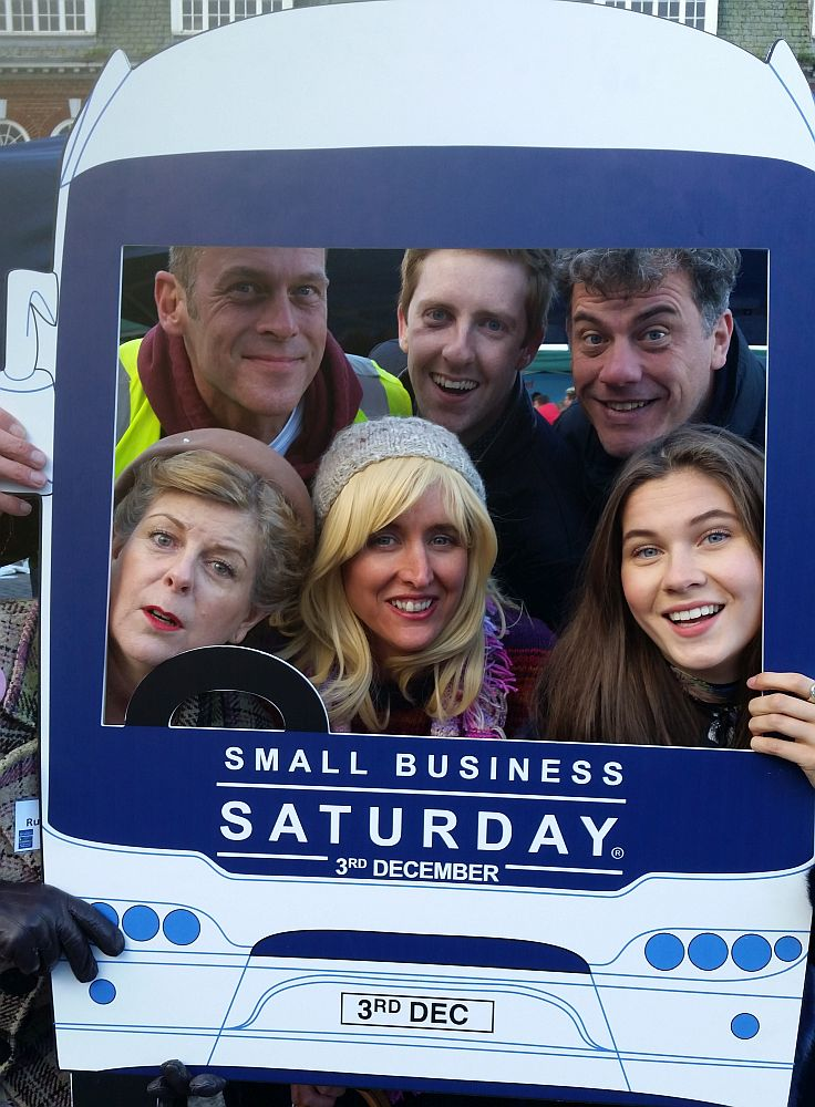 A group look through the windscreen of a cardboard cut out of a bus, stating 'Small Business Saturday'