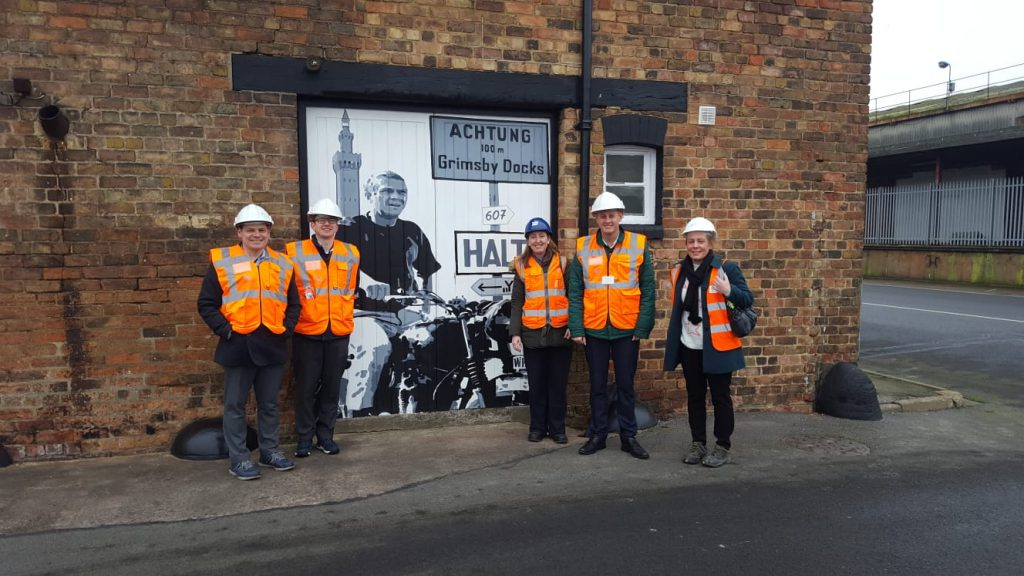 Members of North East Lincolnshire Council in front of a wall art mural.  The mural depicts a scene from the Movie 'The Great Escape' with a motorcyclist in front of the Dock Tower and a sign saying 'Achtung 100m Grimsby Docks'.