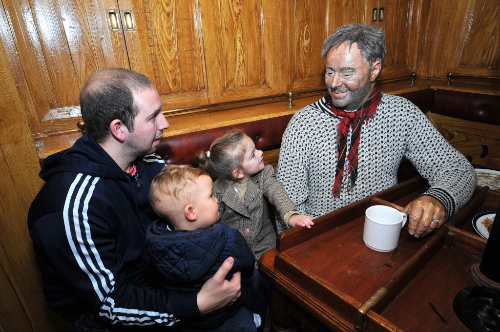 A family looking at a model of a trawlerman drinking a hot drink at the Fishing Heritage Centre