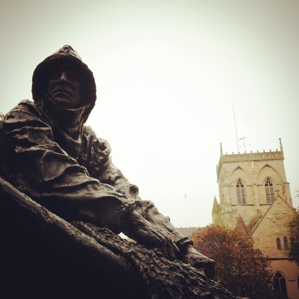 A close-up of the Fisherman's Statue, with Grimsby Minster in the background