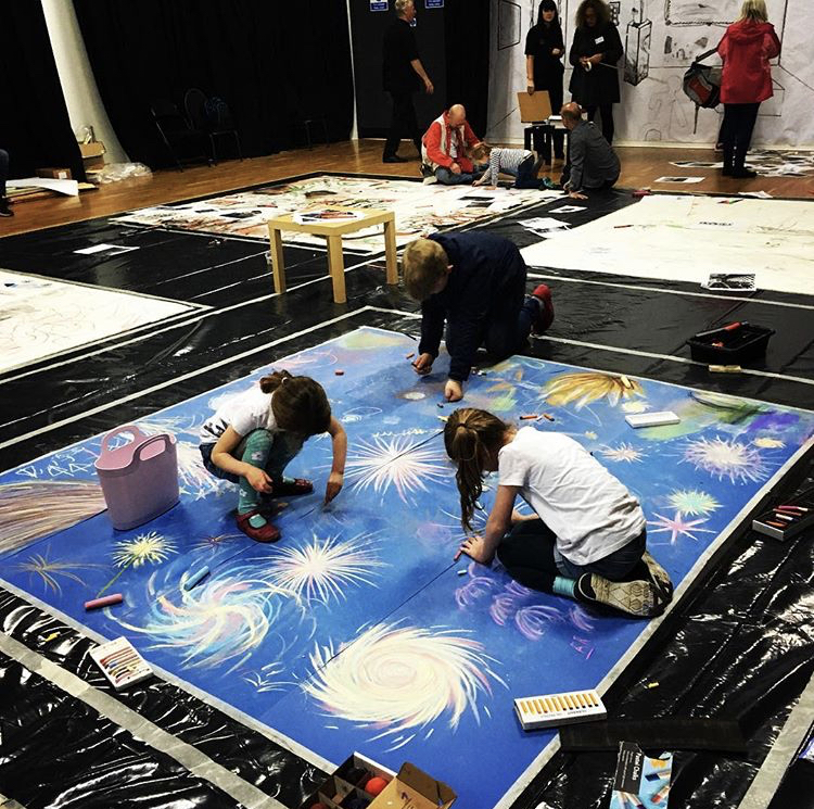Children creating some large colourful artwork on a floor canvass.