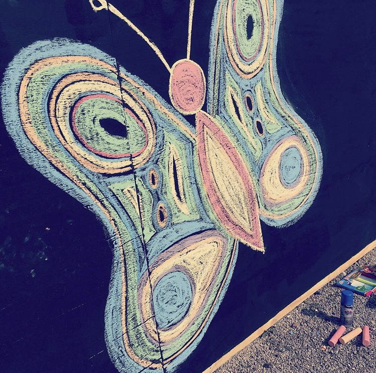 A butterfly drawn on a wall in chalk.