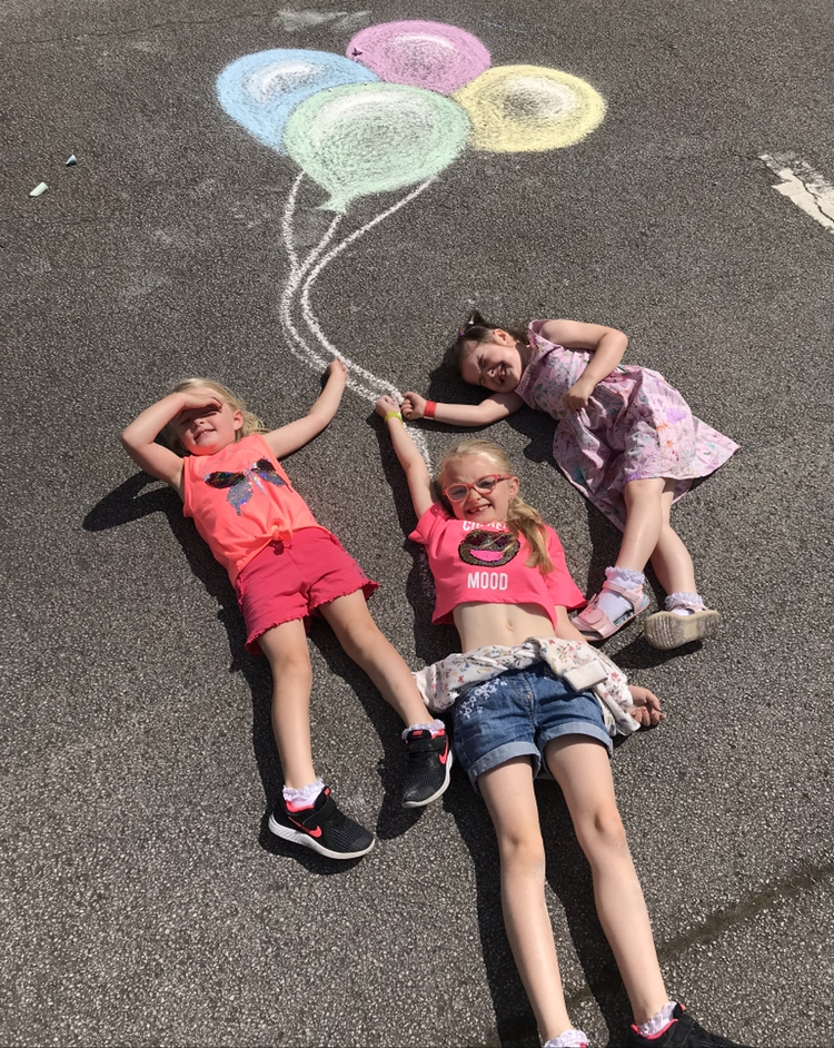 Children laying on the floor pretending to hold colourful balloons drawn on the floor in chalk
