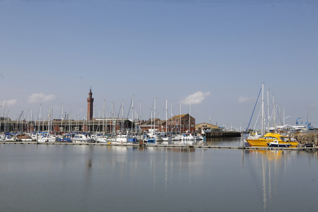 Several boats on Grimsby's Marina with the Dock Tower in the background.