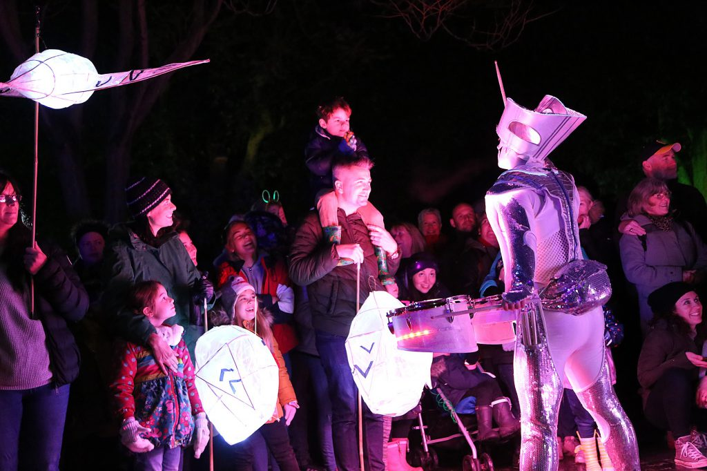 What looks to be a tin man performs to an audience