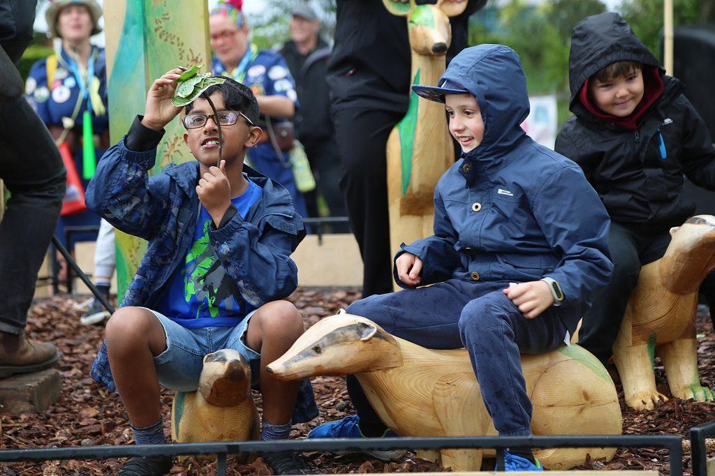 Children sitting on wooden carved animals including a badger