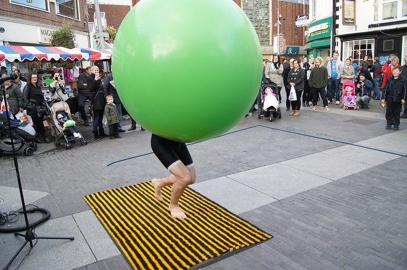 A person with a huge green ball on their head