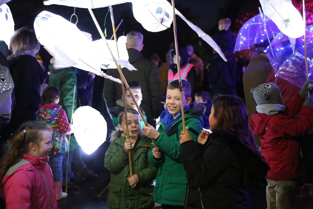 Children hold onto sticks with lit up bird-like models