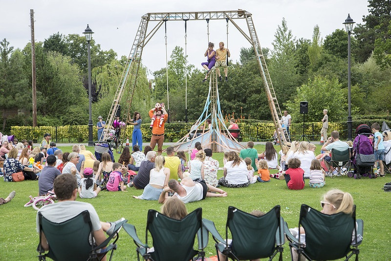 People on tall swing structures being watched by an audience