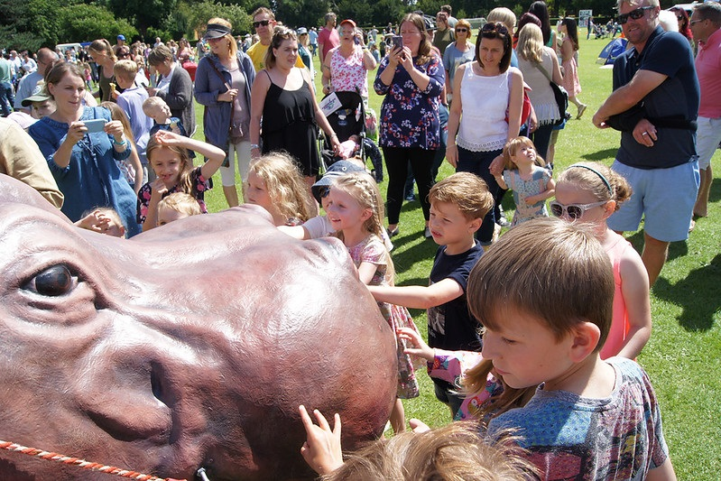 Children playing in a park with a to scale hippo
