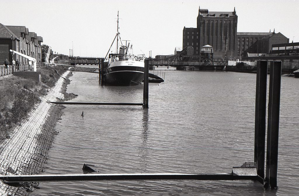 A black and white shot of the Ross Tiger trawler, with Victoria Mill in the background.