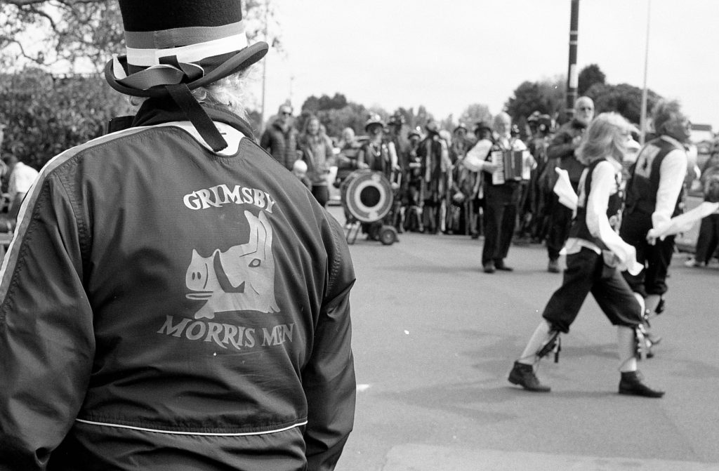 A Morris dance with a person in a 'Grimsby Morris Men' jacket looking on